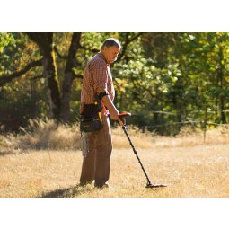 Older gentleman using White's MX7 Metal Detector in a grassy field while wearing all brown