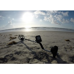 White's TREASUREmaster Metal Detector resting on sand with ocean in background