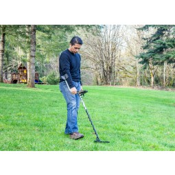 Man in jeans using White's TREASUREmaster Metal Detector in thick grass