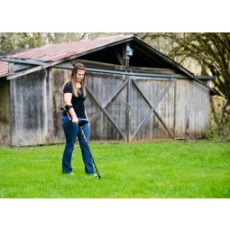 Young lady using White's TREASUREpro Metal Detector near old wooden barn