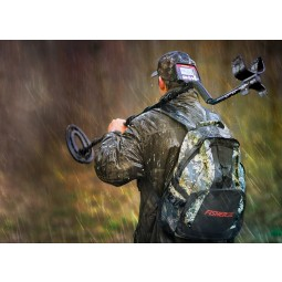 Man carrying Fisher F22 Weatherproof Metal Detector over his shoulder in the rain