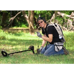 Man in a hat kneeling on the ground with ACE 250 metal detector