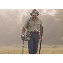 Man with Garrett AT Pro metal detector in foggy field