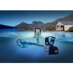 Minelab CTX 3030 Standard Metal Detector with Wireless Headphones totally submersed under water with beach shack in background