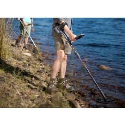 Two people standing near a stream shore using Minelab CTX 3030 Standard Metal Detector with Wireless Headphones