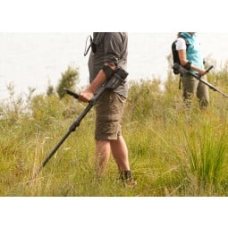 Man and woman using Minelab CTX 3030 Standard Metal Detector with Wireless Headphones in tall grass