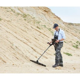 Man using OKM eXp 6000 Professional Metal Detector at bottom of sandy hill