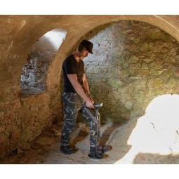 OKM Evolution NTX Metal Detector being used by a man in an underground bunker