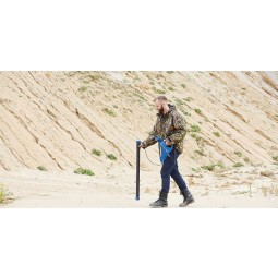 Man walking near sandy hill holding OKM Rover C4 Metal Detector