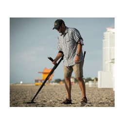 Man wearing a hat using Minelab GO-FIND 22 Metal Detector on a beach