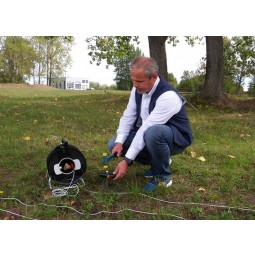 Man kneeling down using a OKM GeoSeeker Mini Water and Cavity Detector in grass