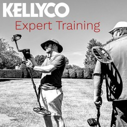 Black and White Image of Two Metal Detectorists Standing in Grassy Field Holding Metal Detectors, Setting them Up with Kellyco in White Lettering Above Red Letters that Read Expert Training