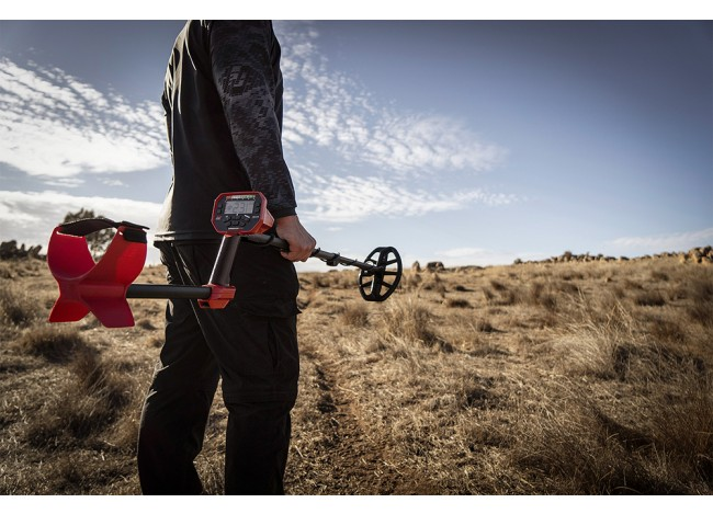 Man standing on a hill holding a Minelab Vanquish 540 Metal Detector