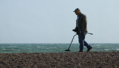 Man on the beach holding one of Best Metal Detectors of 2020 for sale from Kellyco Metal Detectors