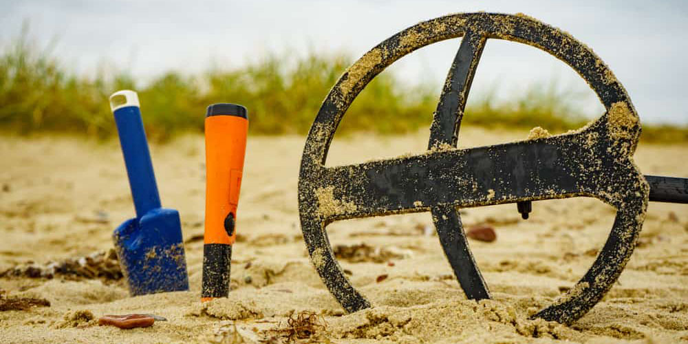 A coil, pinpointer and trowel in the sand