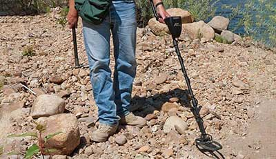 Gold metal detectors used in rocky soil by man holding gold pick