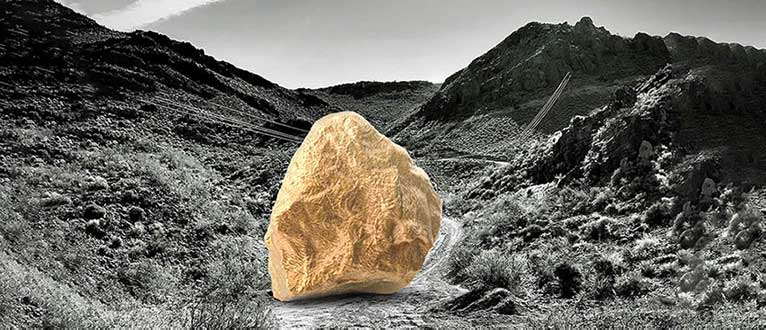 Gold nugget on black and white mountainous background