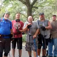 Group of Men Holding Metal Detectors and Diggers Standing in Half Circle with Trees and Branches in Background