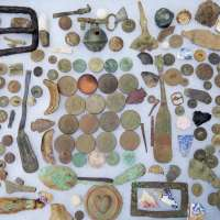 Finds Laid out in a grid-like pattern with coins, bayonet pieces, shards of pottery, brooches, belt buckles and much more all covered in oxidation and dirt laying on white background
