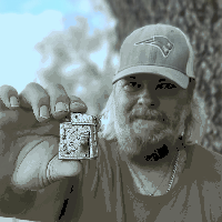 Man Holding Vintage 1940s or earlier Lighter Between Forefinger and Thumb with Man Out of focus in Background Wearing a Hat