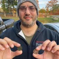 Metal Detectorists Holding Two Coins in Between Forefinger and Thumb with Autumn Leaves in Background and Trees