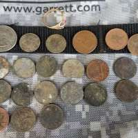Pennies and Coins Lined Up in a Grid with Ring at the Upper Left Corner on Garrett Camo Bag Fabric Background